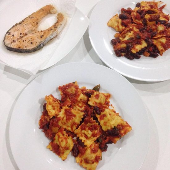 Mushroom ravioli mixed with beans and paprika in arrabbiata sauce and served with grilled salmon